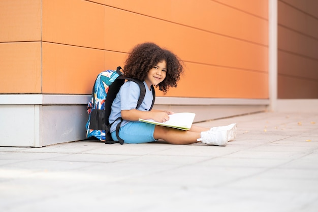 Afro boy with his backpack on is sitting writing in a notebook