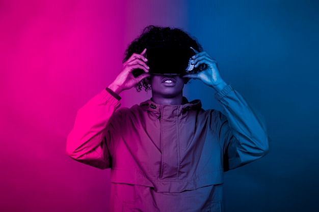Afro boy with vr glasses. a young afro immersed in virtual reality makes movements with his hands. blue and red light falls on a boy.