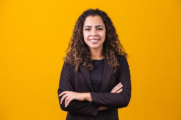 アフロビジネスウーマン。黄色の背景、水平バナー、ワイドロングショット、パノラマで腕を組んでポーズをとってスーツの自信を持って黒人女性