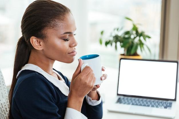 オフィスでお茶とテーブルのそばに座っている青いドレスのアフロビジネス女性。