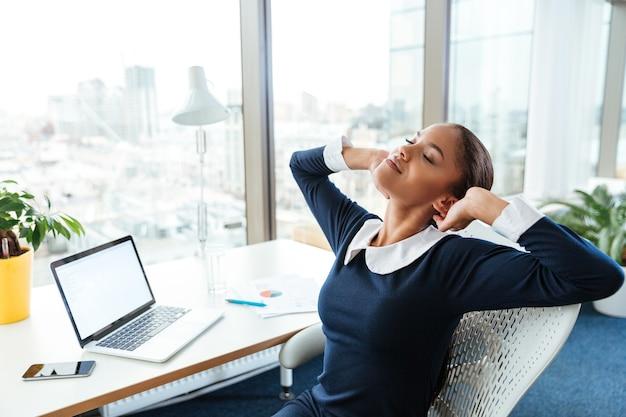 窓の近くのテーブルのそばに座って、オフィスでストレッチドレスを着たアフロビジネス女性