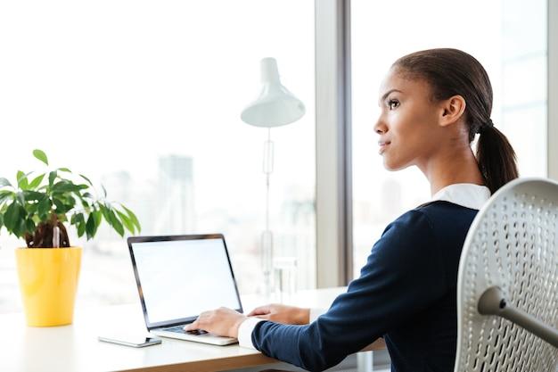 ノートパソコンで窓の近くのテーブルのそばに座って、オフィスで脇を見ているドレスを着たアフロビジネス女性