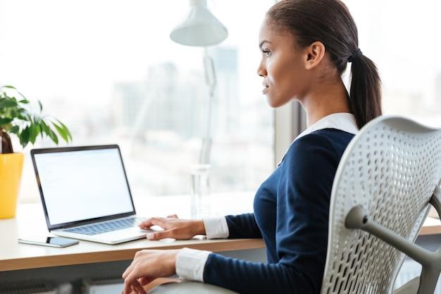 ノートパソコンで窓の近くのテーブルのそばに座っているドレスを着たアフロビジネス女性。
