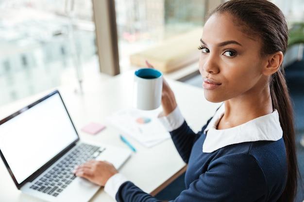 お茶を飲みながら窓際のテーブルのそばに座って、オフィスでカメラを見ているドレスを着たアフロビジネス女性。