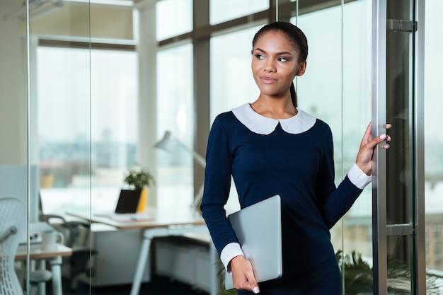 オフィスで手にラップトップを持って立っているドレスのアフロビジネス女性