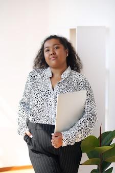 窓際のテーブルに座って、オフィスでラップトップを使用してシャツを着たアフロビジネス女性。