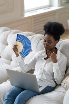 手を振るファンを使用して自宅のリビングルームに座って熱射病に苦しんでいるアフロビジネス女性