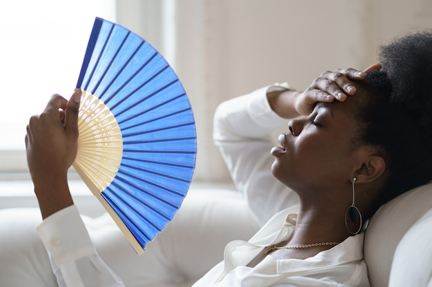 Afro business woman suffering from heat stroke sitting in living room at home using waving fan