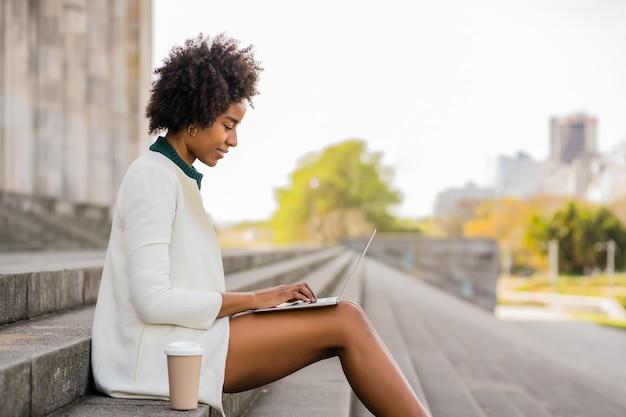 屋外の階段に座っている間彼女のラップトップを使用してアフロビジネス女性。都市とビジネスのコンセプト。