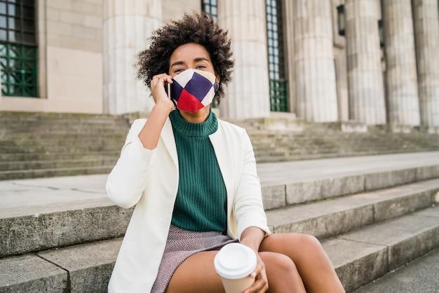 Афро-деловая женщина в защитной маске и разговаривает по телефону, сидя на лестнице на улице. бизнес и городская концепция.