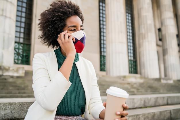 通りの屋外の階段に座って保護マスクを着用し、電話で話しているアフロビジネスウーマン。ビジネスと都市のコンセプト。