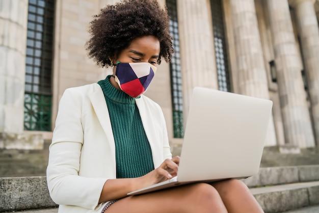 보호 마스크를 착용하고 야외 계단에 앉아있는 동안 그녀의 노트북을 사용하는 아프리카 비즈니스 여자