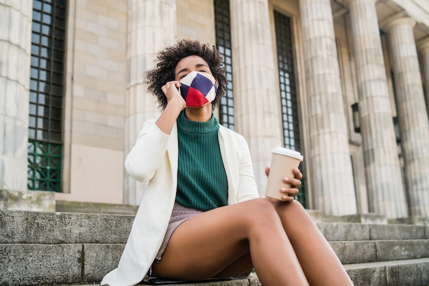 Afro business woman wearing protective mask and talking on the phone while sitting on stairs outdoors at the street. business and urban concept.