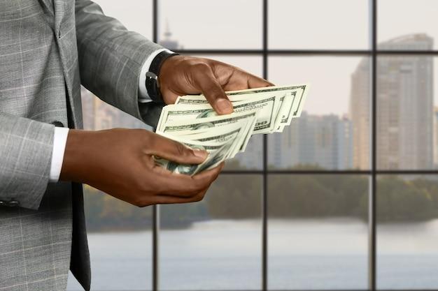 Руки афро-бизнесмена, считающие деньги. менеджер с деньгами в дневное время. подумайте о том, чтобы поделиться своим богатством. большой город дает большие возможности.