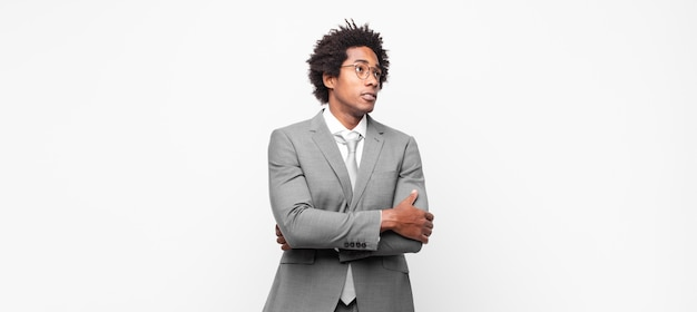Afro businessman doubting or thinking, biting lip and feeling insecure and nervous, looking to copy space on the side