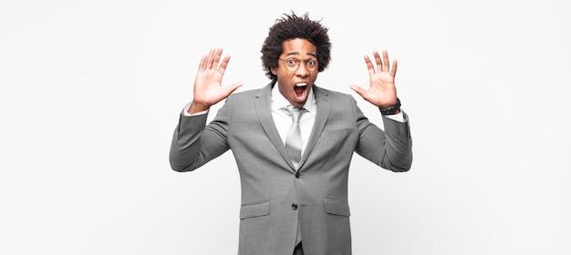 Афро-бизнесмен кричит в панике или гневе, шокирован, испуган или разъярен, положив руки на голову