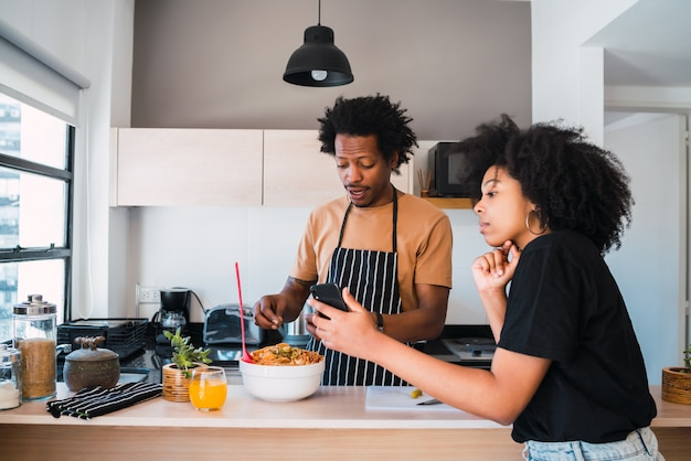 Afro couple cooking together and using phone at home.