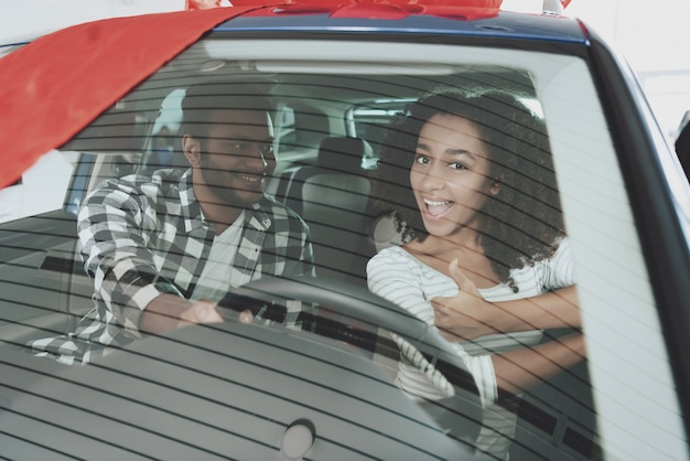 Afro couple inside car girl at steering wheel.