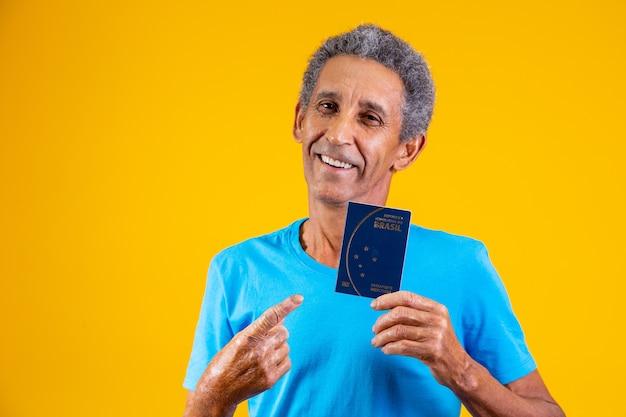 Афро пожилой мужчина держит в руках бразильский паспорт.