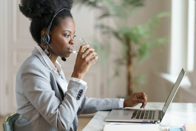 Afro employee woman looking at laptop screen, working at home office, drinking water from a glass.