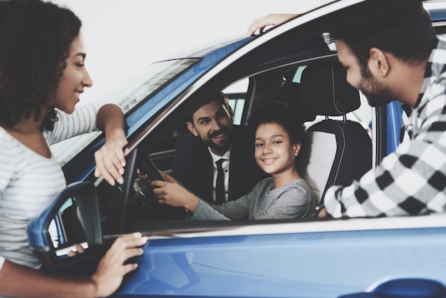 Afro family buying car happy kid on driver seat