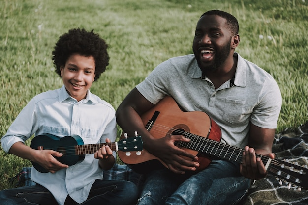 Afro father and afro son play on guitars on picnic.