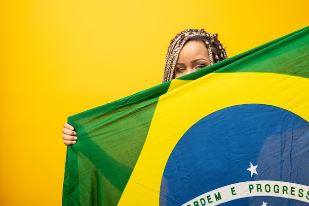 Afro girl cheering for favorite brazilian team, holding national flag in yellow.