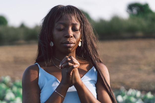 アフロガールは目を閉じ、屋外で祈っていました。信仰、精神性、宗教のための祈りの概念に手を組んでいます。アフリカの民族性