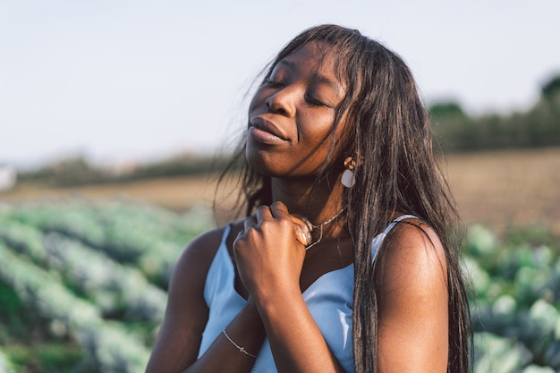 Afro girl closed her eyes, praying outdoors. hands folded in prayer concept for faith, spirituality and religion. african ethnicity