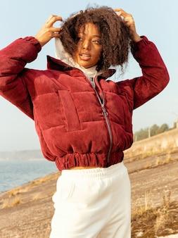 赤いジャケットとモダンな白いパンツのアフロガール、ファッショナブルな外観。輝く明るい笑顔、スリムなボディ、ボリュームのある巻き毛。秋の寒さ、暖かい服。アウトドア