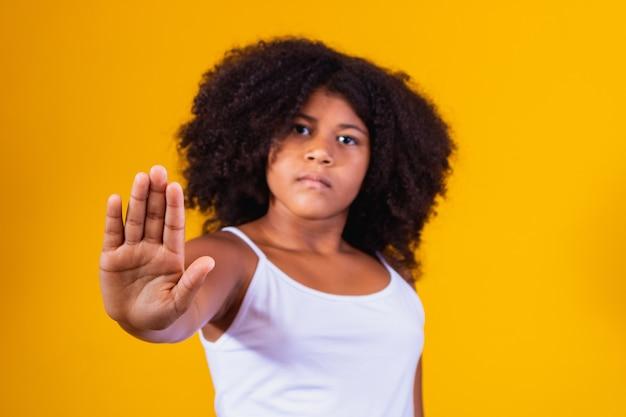 一時停止の標識を作るアフロの女の子