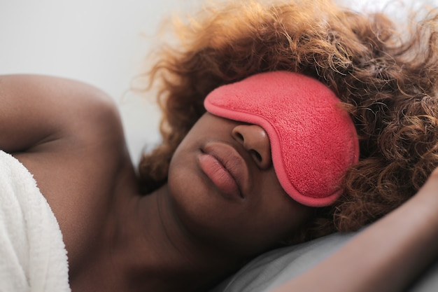 Afro girl sleeping with a mask