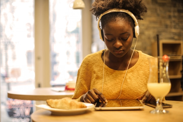 Afro girl using a tablet in a bistro