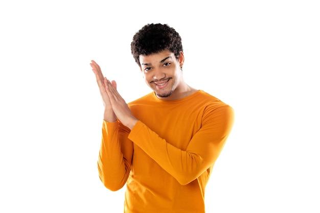 白い背景で隔離のオレンジ色のセーターの拍手をしているアフロ男