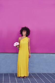 Афро-волосатая женщина-мулатка в желтом платье и фиолетовом фоне.