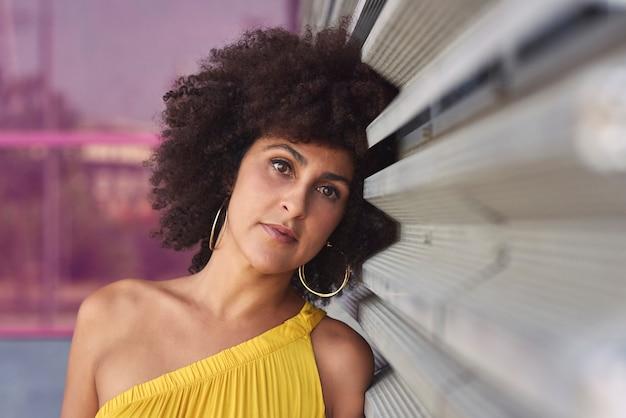 黄色のドレスと紫の背景のアフロ髪のムラートの女性。