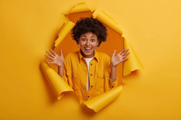 Afro hairstyle keeps palms raised, enjoys pleasant news, has natural curly hair, shows excitement and happiness, stands in ripped hole of yellow paper wall