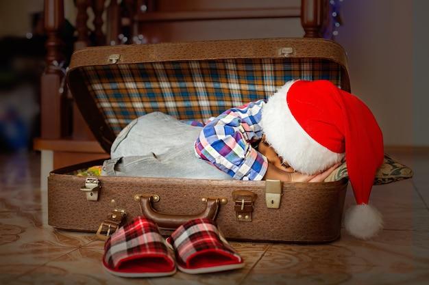 Афро-ребенок спит в чемодане. маленький санта спит в чемодане. время просыпаться. настал праздник.