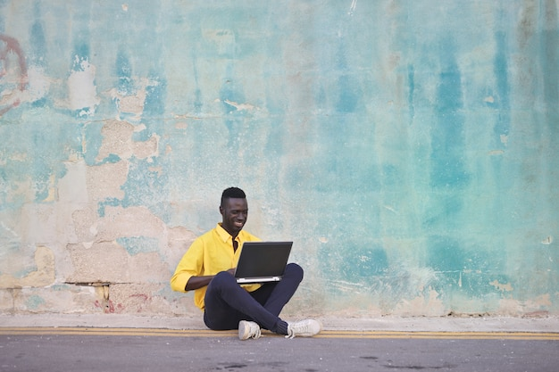 Afro man happily using a laptop