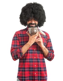 コーヒーの入った瓶ガラスを内側に持つアフロ男