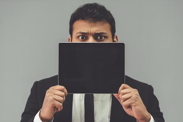 古典的なスーツを着たアフロ男はデジタルタブレットを保持しています。