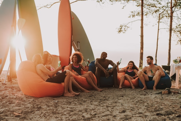 Afro man is resting with friends on beach.