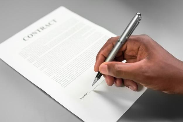 계약에 서명 하는 아프리카 남자. 큰 돈을 대출. 조심하세요. 돌아갈 길은 없다.