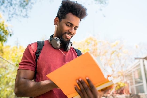 Афро человек студент изучает и читает его книгу.