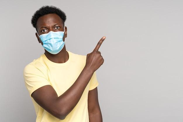 Афро-мужчина в маске для лица указывает пальцем, показывая на пустое место для копирования. covid-19 пандемия.