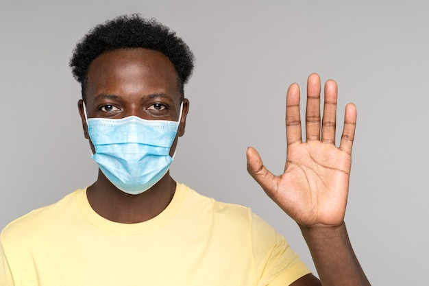 Afro man wear protective face mask to safe from coronavirus covid-19 showing rising palm up isolated