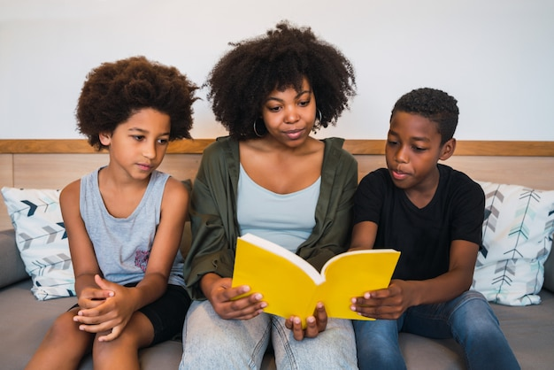 Afro mother reading a book to her children.