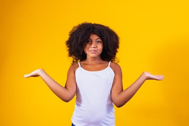 혼란스러운 표정과 팔과 제기 손으로 우둔 한 고립 된 배경에 아프리카 예쁜 여자. 의심 개념입니다.