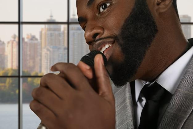 Афро-певица держит микрофон.