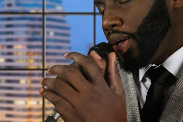 Афро-певица с закрытыми глазами.